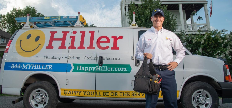 technician holding toolbag in front of van