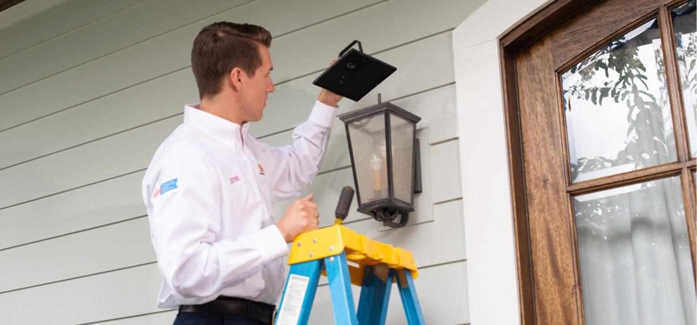 Hiller technician fixing exterior light