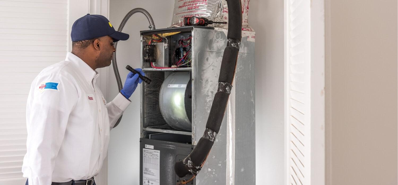 HVAC Technician Looking At A Faulty Fan In The Furnace