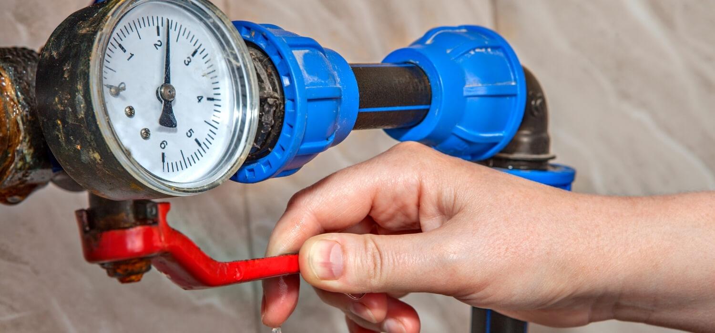 Hand Turning Off Water Shutoff Valve